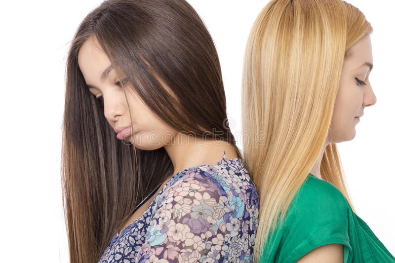 Closeup portrait of two bored teenage girls standing back to back stock images