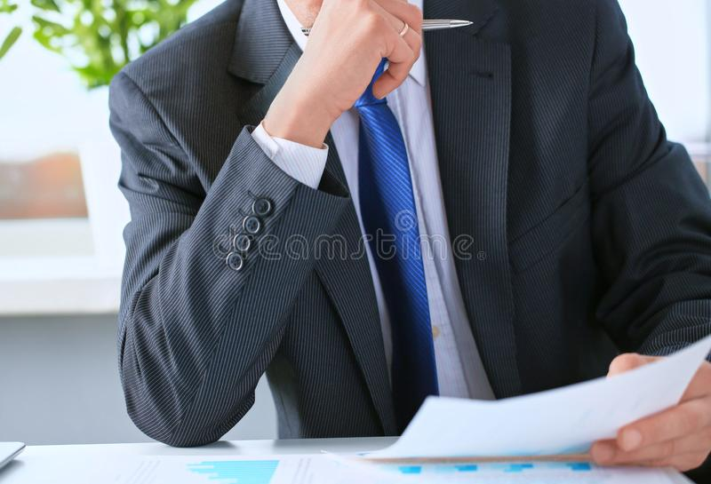 Closeup portrait of unrecognizable businessman in black formal s. Uit and blue tie reading contract documents at the desk in the office stock photos