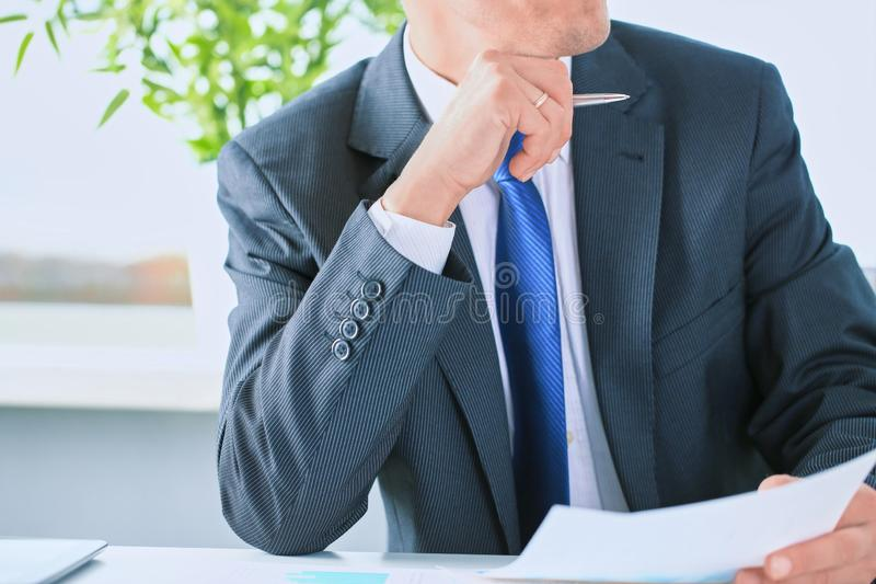 Closeup portrait of unrecognizable businessman in black formal s. Uit and blue tie reading contract documents at the desk in the office stock images