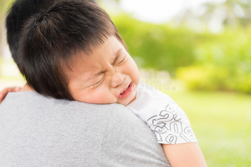 Closeup portrait of upset little girl crying on her mothers shoulder stock photo