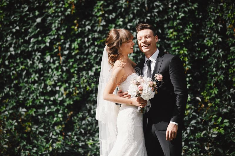 Closeup Portrait of wedding bride and groom with bouquet posing by the old cathedral. Bride and groom royalty free stock photos