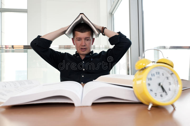 Closeup portrait of white man surrounded by tons of books, alarm clock, stressed from project deadline, study, exams stock image