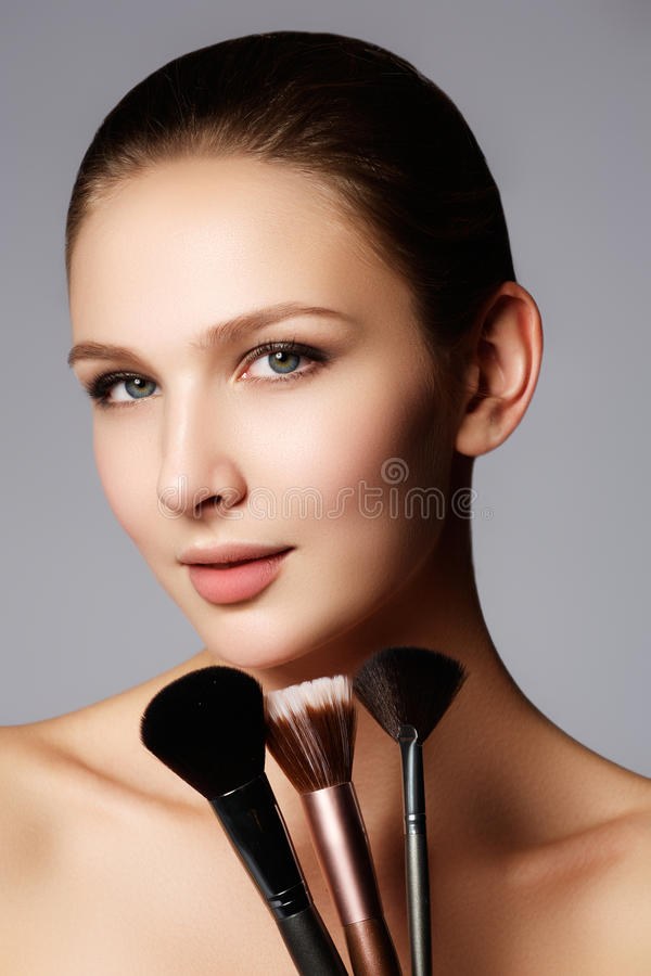 Closeup portrait of a woman applying dry cosmetic tonal foundation on the face using makeup brush. Beautiful woman with makeup br royalty free stock images