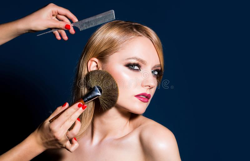Closeup portrait of a woman, cosmetic tonal foundation on face, makeup brush. omb the girl hairbrush. Makeup in process. Female portrait isolated on black stock images