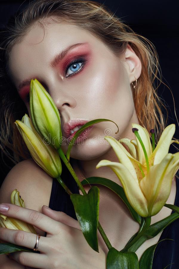 Closeup portrait of woman with flowers lilies in his hands, bright contrasting makeup on the girl`s face. Wet hair and clean stock photo