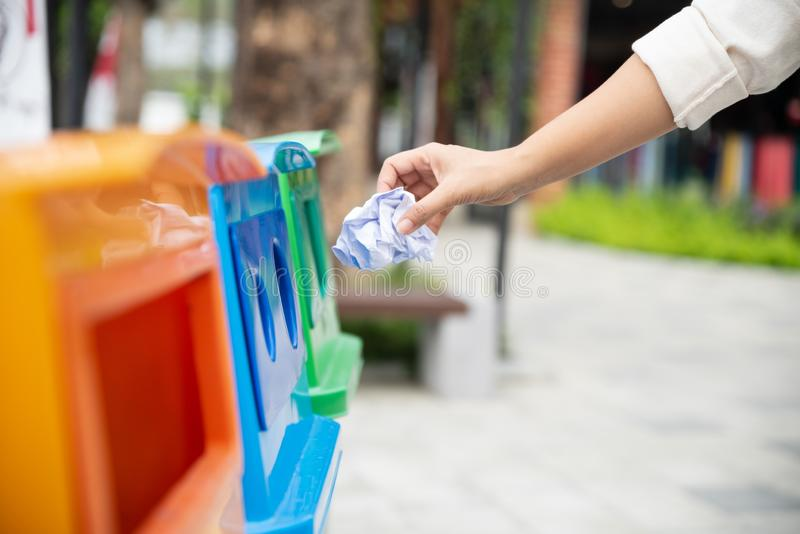 Closeup portrait woman hand throwing crumpled paper in recycling bin stock image