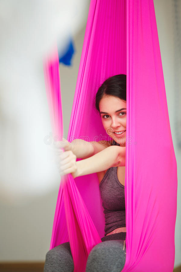 Closeup portrait of woman posing in hammock, aerial antigravity yoga. Closeup portrait of woman posing in pink silk hammock, aerial antigravity yoga exercise stock images