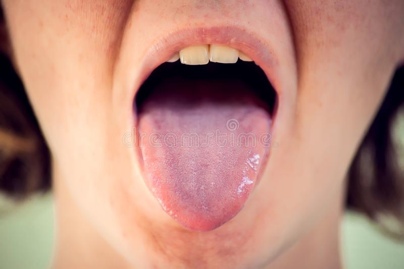 Closeup portrait of young woman showing her tongue royalty free stock photography