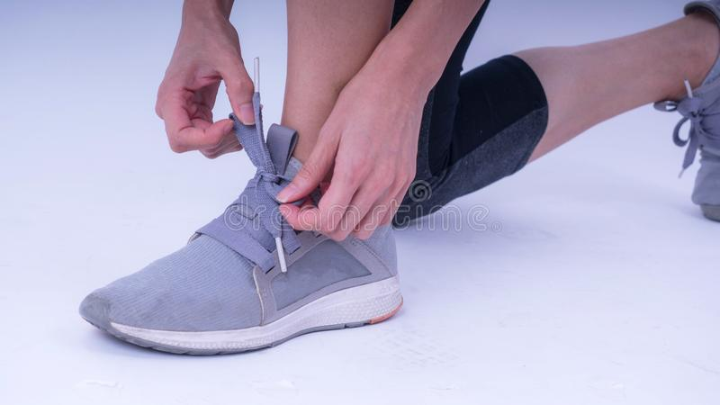 Closeup portrait of a woman tying shoelaces, Beautiful woman tying shoelaces isolated over white background royalty free stock image