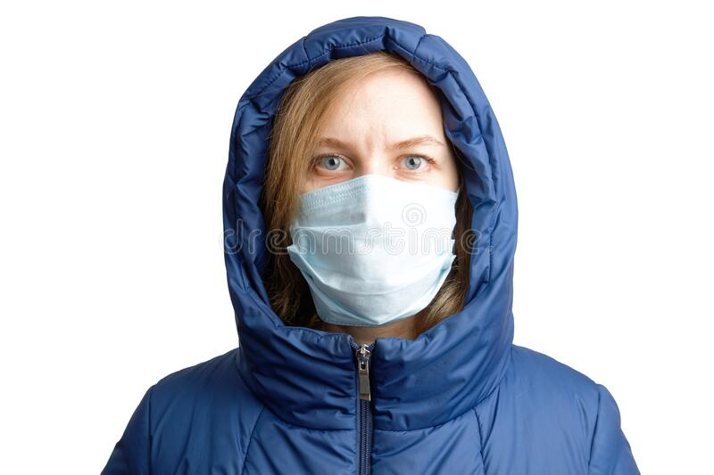 Closeup portrait of a woman in winter clothes and a protective mask royalty free stock photos