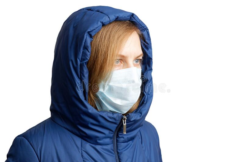 Closeup portrait of a woman in winter clothes and a protective mask. Isolated on white stock photo