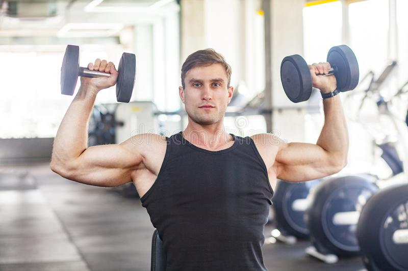 Closeup portrait of young adult man muscular built handsome athlete working out in a gym, sitting and holding two dumbbell with stock image