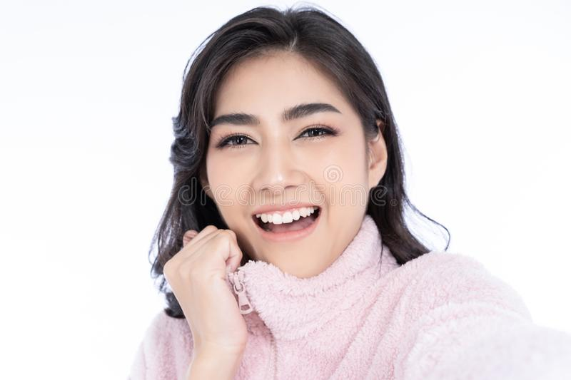 Closeup portrait of young Asian lady wearing knitted sweater pink cold smilling and taking selfie isolated over white background. stock photos