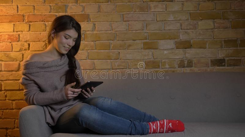 Closeup portrait of young attractive caucasian female using the tablet while resting laidback on the couch and smiling. Happily indoors at cozy home indoors royalty free stock images