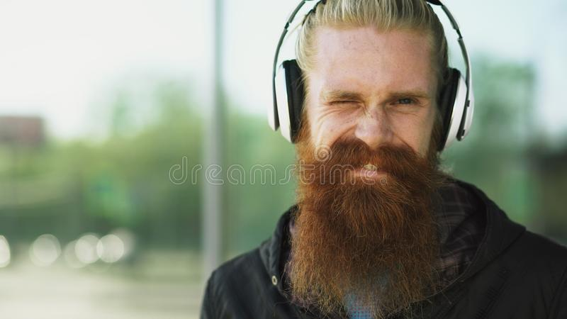 Closeup portrait of young bearded hipster man with headphones listen to music and smiling at city street stock photo