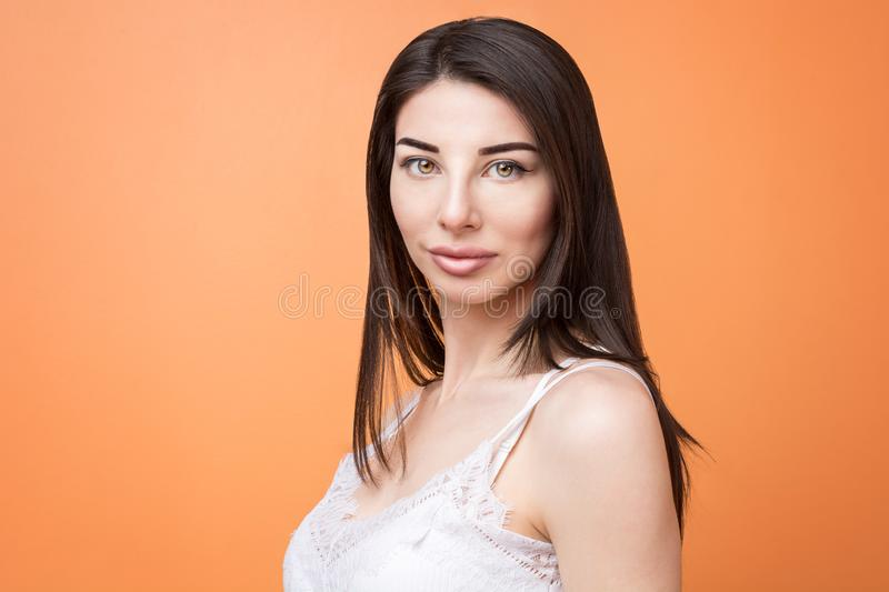Closeup portrait of a young beautiful brunette woman holding looking at the camera against orange background stock images