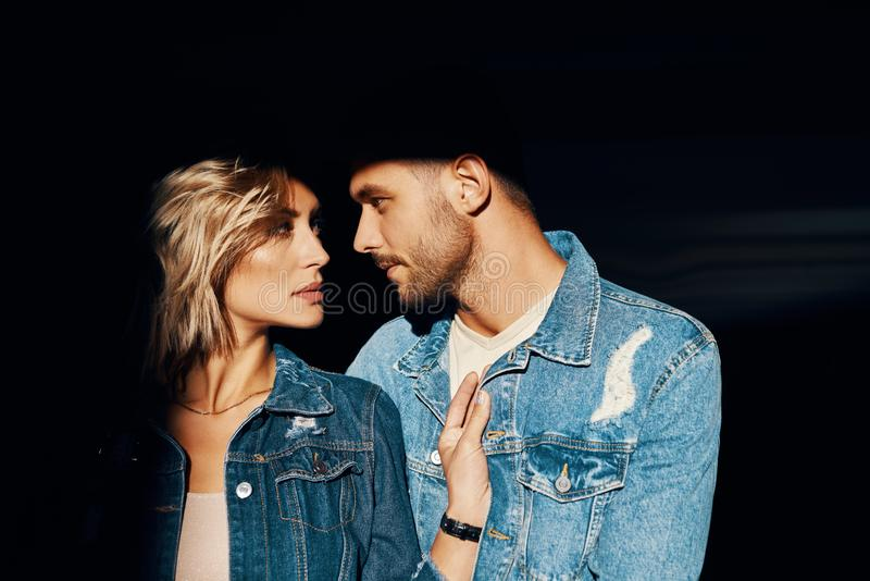 Closeup portrait of young and beautiful couple wearing denim jeans stock images