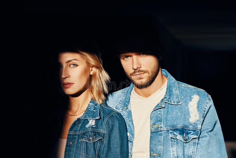 Closeup portrait of young and beautiful couple wearing denim jeans stock photography