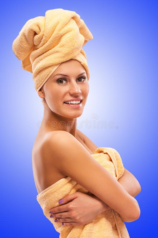Closeup portrait of young beautiful woman after bath. On blue background royalty free stock photos