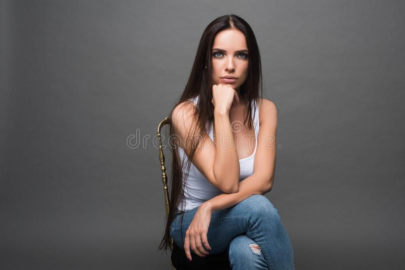 Closeup portrait of young beautiful woman with with beautiful long hair. Sitting and posing in studio. Portrait of trendy, cheerfu royalty free stock photography