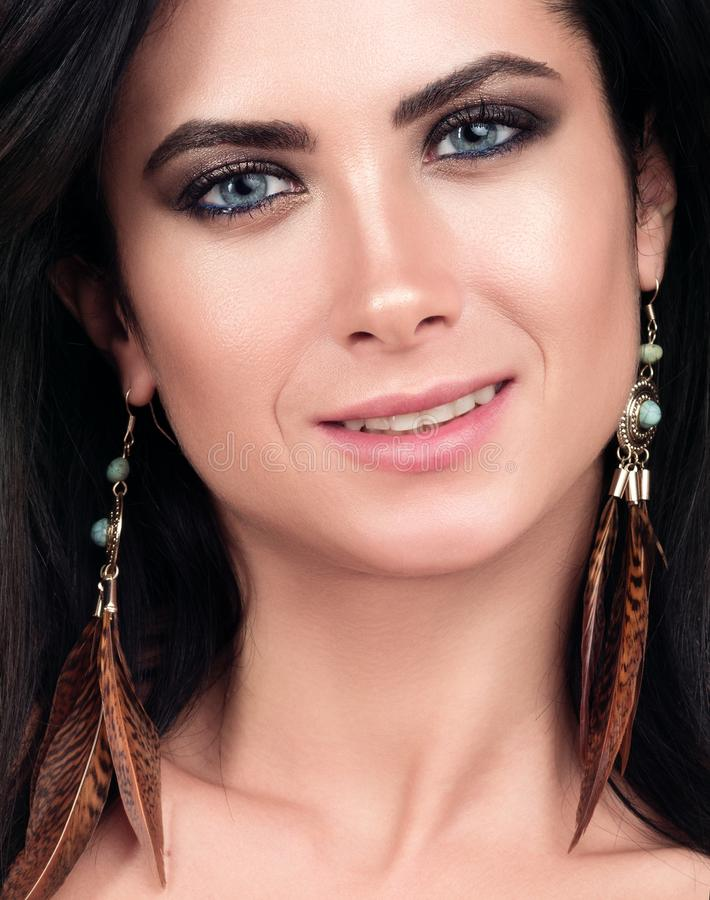 Closeup portrait of young beautiful woman. Dark hair, blue eyes and nude makeup stock photography