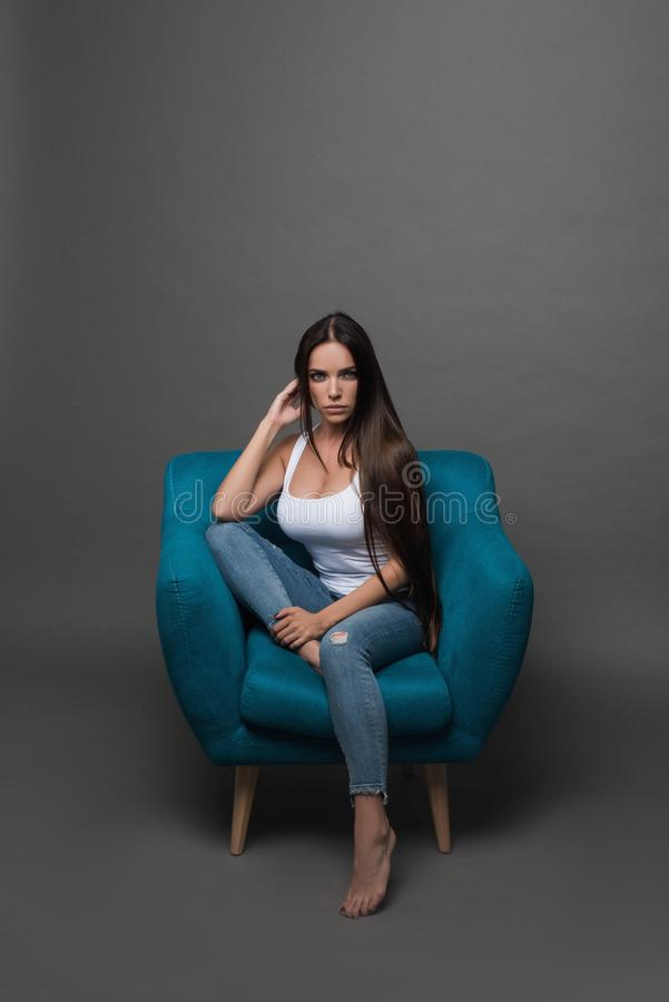 Closeup portrait of young beautiful woman with with beautiful long hair. Sitting and posing in studio. Portrait of trendy, cheerfu royalty free stock photos