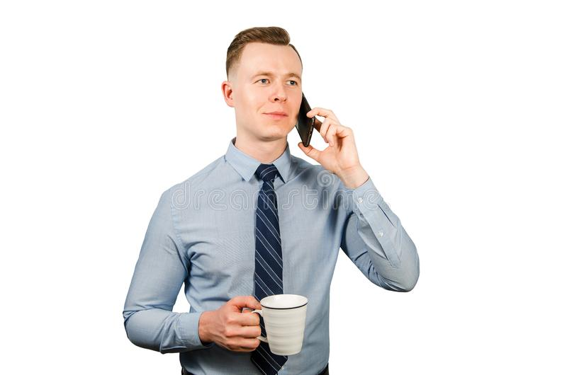 Closeup portrait of young businessman dressed in blue shirt and tie, talking on the mobile phone, isolated on white background stock photos