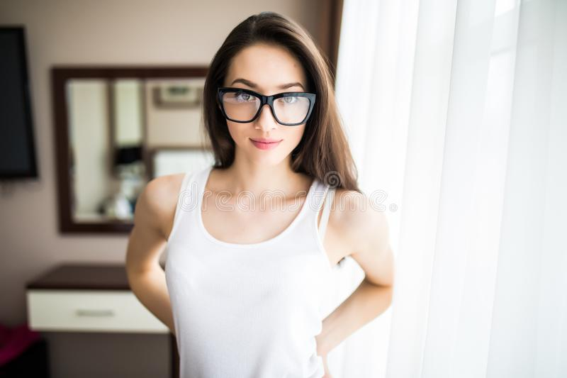 Closeup portrait of a young cheerful woman in glasses at home royalty free stock photos