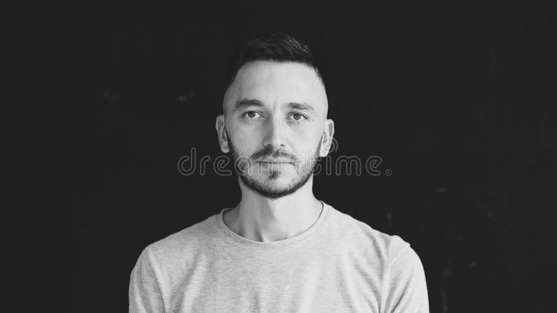 Closeup portrait of young concentrated man looking at camera on black background royalty free stock photo