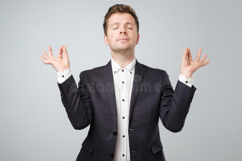 Closeup portrait of young handsome male in suit, in meditation pose, relaxing, in zen, isolated on white background royalty free stock images