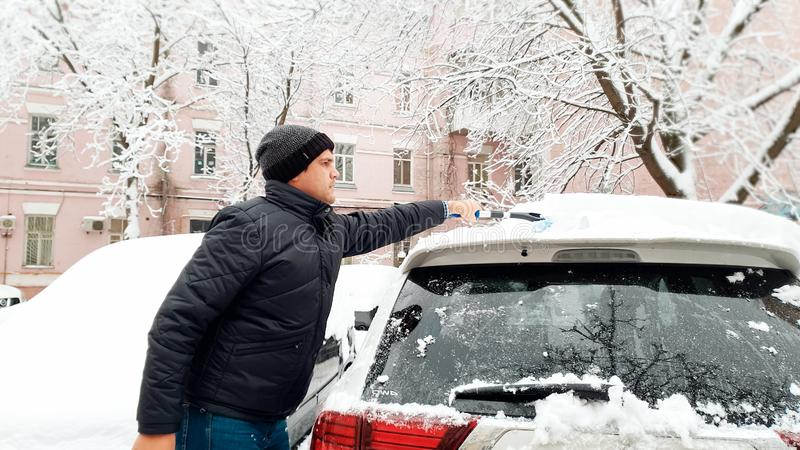 Closeup portrait of young handsome man in black coat and hat trying to clean up snow covered white car after blizzard royalty free stock photography