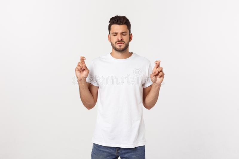Closeup portrait of young handsome man crossing fingers, wishing, praying for miracle, hoping for the best, isolated on stock image