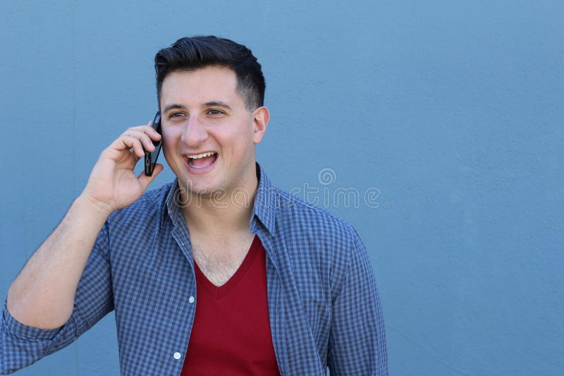 Closeup portrait, young happy ecstatic man with wide open mouth talking on cell phone, isolated on blue background.  stock images