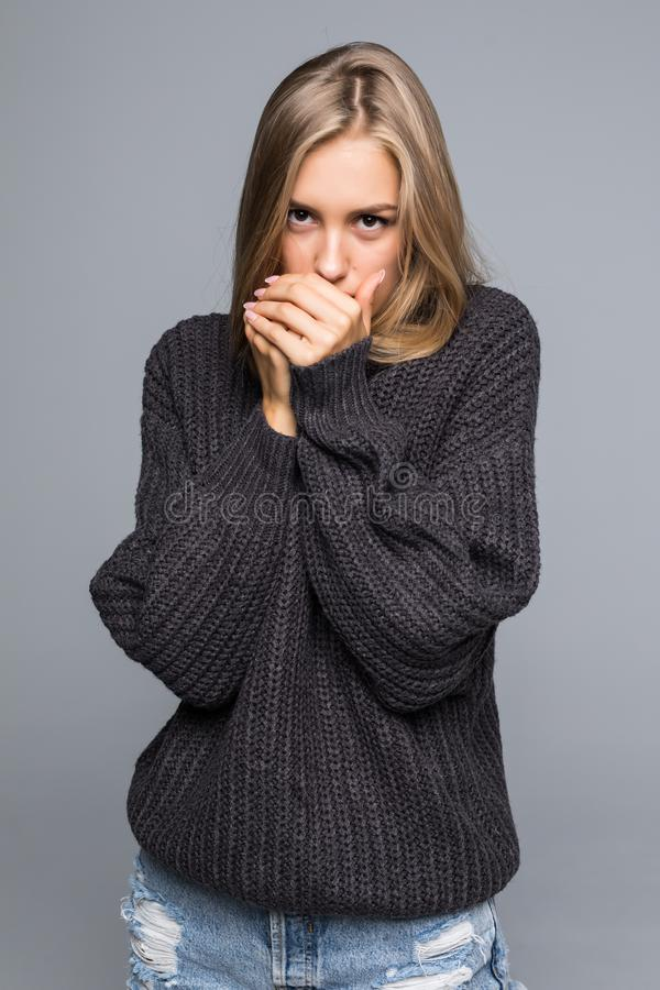 Portrait of a young happy woman in warm winter outfit on gray background stock photos