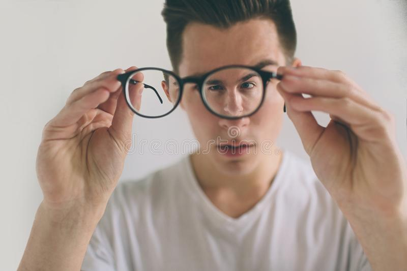 Closeup portrait of young man with glasses. He has eyesight problems and is squinting his eyes a little bit. Handsome. Guy is holding his eyeglasses right in royalty free stock images
