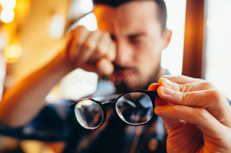 Closeup portrait of young man with glasses, who has eyesight problems royalty free stock photos