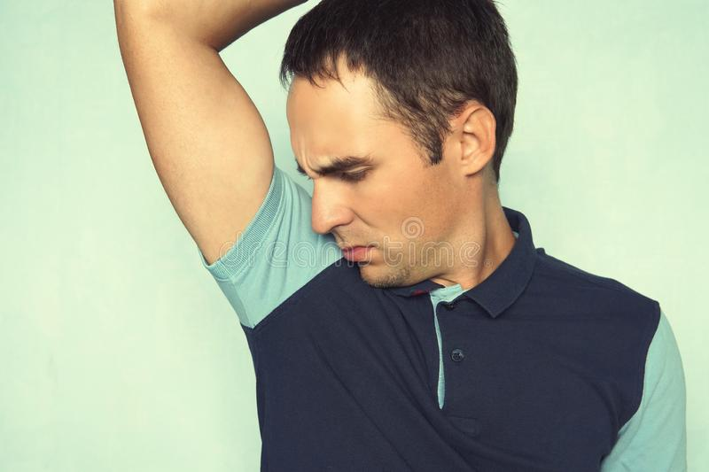 Closeup portrait of young man, smelling, sniffing his armpit, something stinks, very bad, foul odor situation, on blue wall backgr stock photography