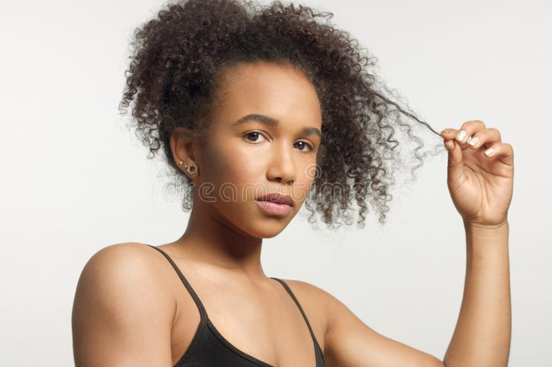 Closeup portrait s of young mixed race model with curly hair in studio with natural neutral makeup royalty free stock photos