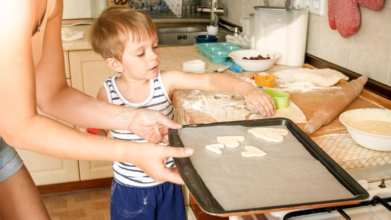 Closeup portrait of young mother teaching her toddler son making cookies. Child with parent baking desserts on baking stock images