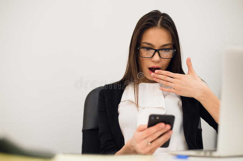 Closeup portrait young, shocked business woman, looking at cell phone seeing bad text message, email, isolated indoors royalty free stock photography