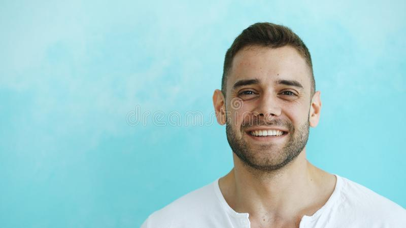 Closeup portrait of young smiling and laughing man looking into camera on blue background stock images