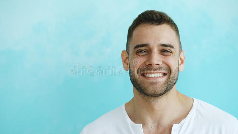 Closeup portrait of young smiling and laughing man looking into camera on blue background stock photography