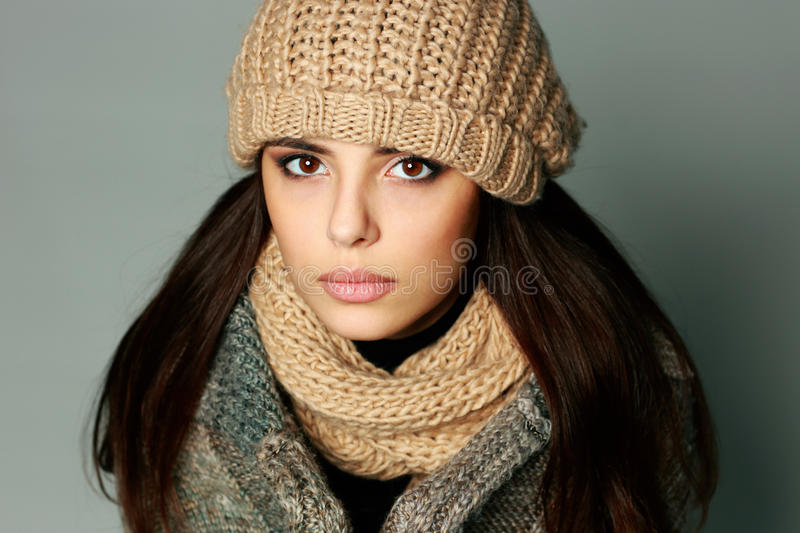Closeup portrait of a young thoughtful woman in warm winter outfit. On gray background royalty free stock image