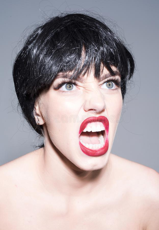 Closeup portrait of young woman with full red lips and big green eyes wearing black wig isolated on gray background stock photo
