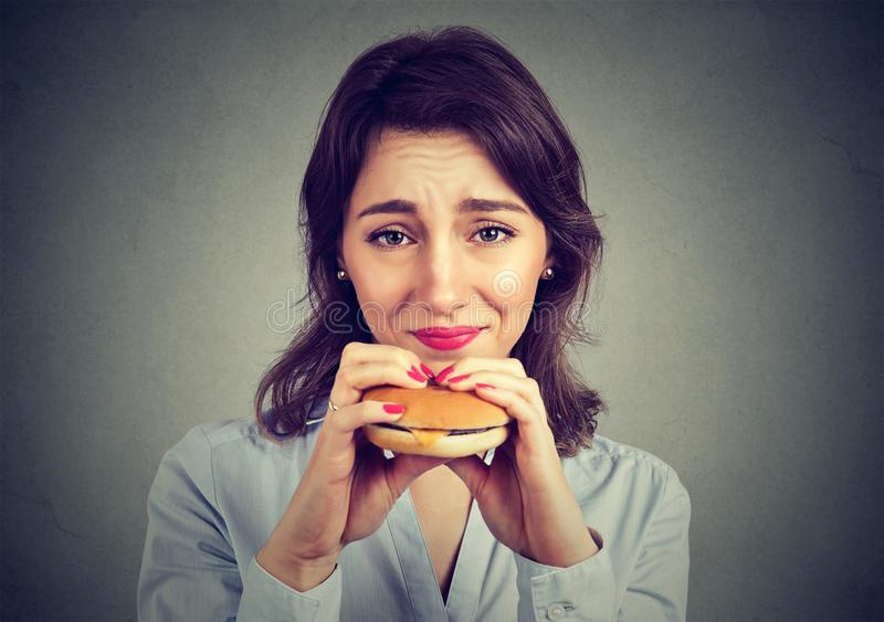 Woman with guilty feeling to eat a hamburger. Closeup portrait of a young woman with guilty feeling to eat a hamburger stock image