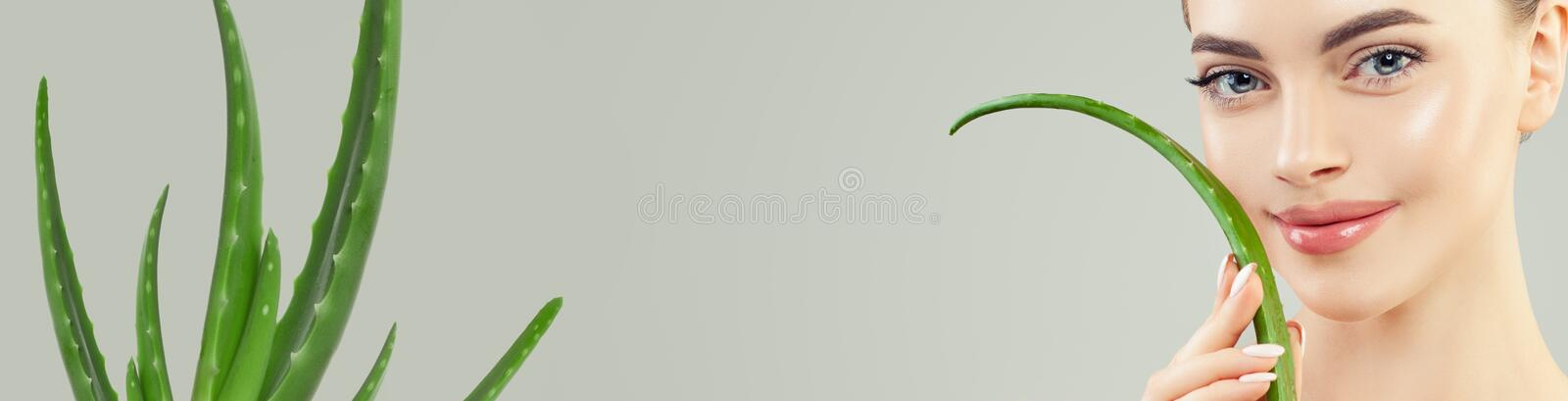 Closeup portrait of young woman with healthy skin and green aloe vera leaf in her hands, skincare concept royalty free stock photo