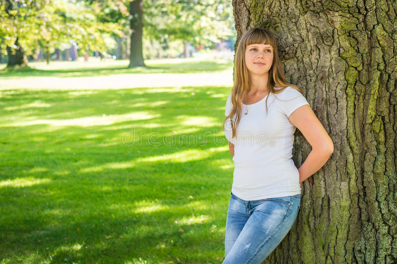 Closeup portrait of young woman near tree royalty free stock photos