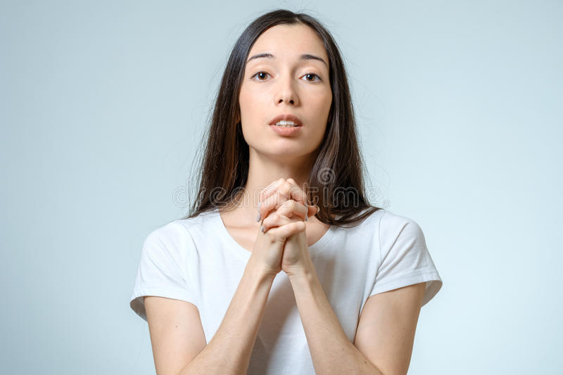 Closeup portrait of a young woman praying royalty free stock photo