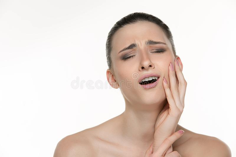Closeup portrait of young woman suffering from terrible tooth pain, touching pressing her cheek. Dental care and stock image