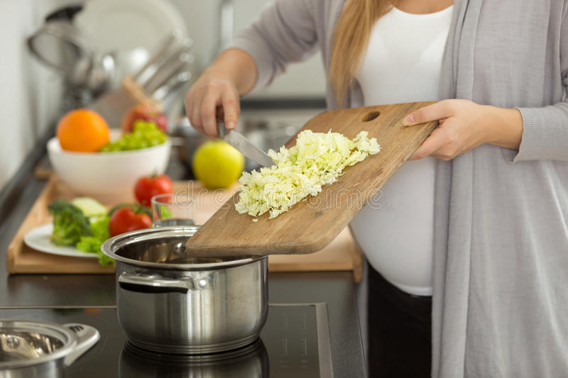 Closeup of pregnant woman cooking vegetable soup royalty free stock images
